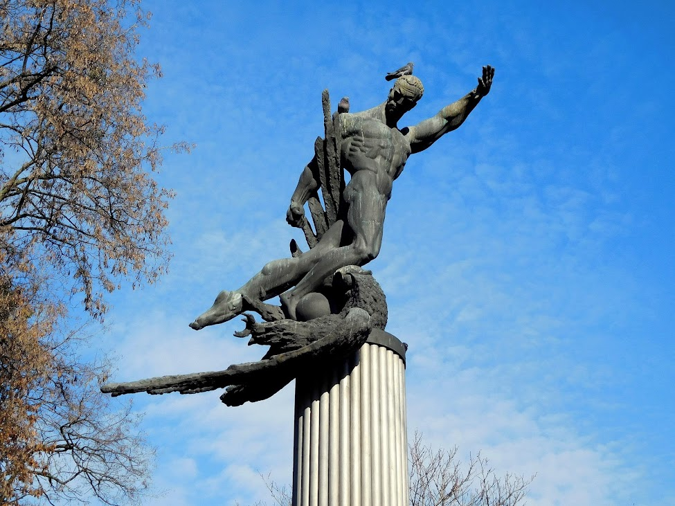 """Ein Mahnmal erinnert an das """"Todesspiel"""", wobei der Adler offenbar Deutschland symbolisiert und hier niedergedrückt wird, von den Knien eines starken Athleten. Dessen Armbewegung weckt Assoziationen; die Friedenstaube auf dem Kopf kam zufällig auf das Bild."""