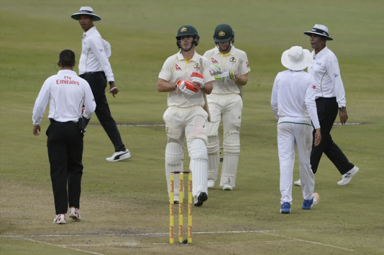 Mitchell Marsh of Australia walks off the pitch along with his batting partner Tim Paine after bad light stopped play during day 1 of the 1st Sunfoil Test match against South Africa at Sahara Stadium Kingsmead on March 01, 2018 in Durban, South Africa.