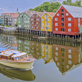 Boat On The River Nid Tronheim Norway by Graham Mulrooney - City,  Street & Park  Historic Districts ( reflection, old, wooden construction, europe, river nid, reflections, pilings, historic, norway, kingdom, trondheim, buildings, kingdom of norway, piles, wood framed, water, warehouses, scandinavia, bakklandet, nid, boats, traditional, structures, horizontal, river,  )