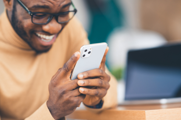 Man laughs and looks at phone