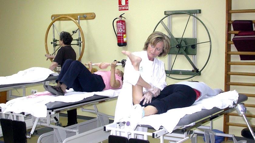 una fisioterapeuta realiza ejercicios de rehabilitación a una paciente.