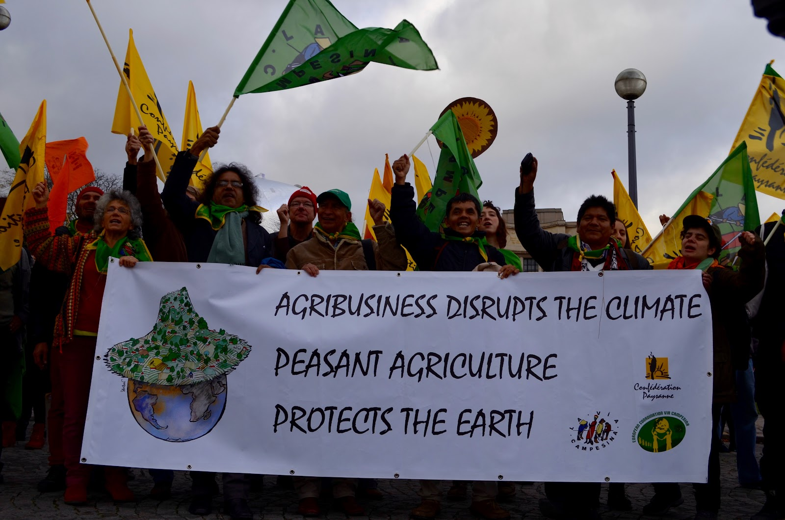 "Protesters holding sign that reads: ""Agribusiness disrupts the climate. Peasant agriculture protects the earth."""