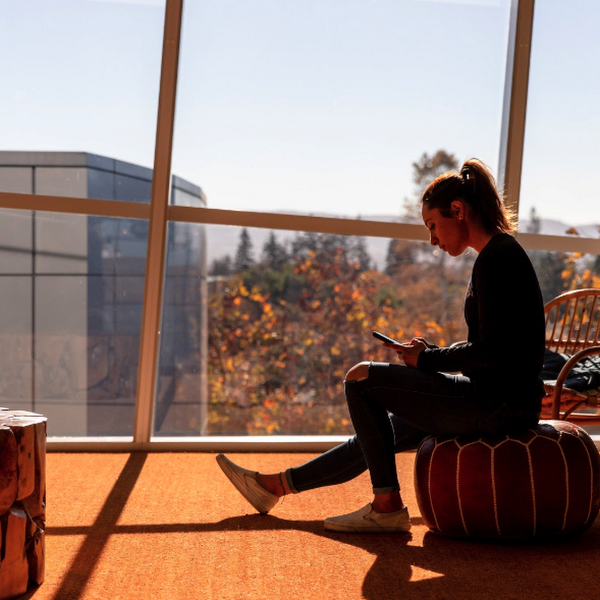 A person uses their phone in a sunny office lounge with modern, natural materials and furniture