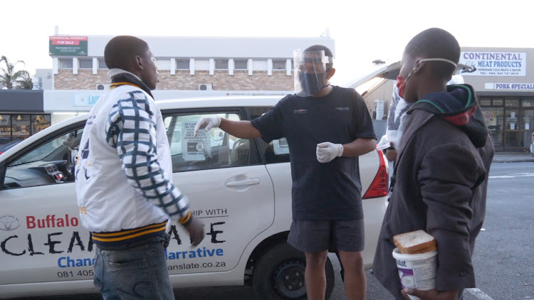 Founder of NPO Clean Slate Brian Francis, centre, offers food to homeless people during a recent lockdown outreach project in East London.