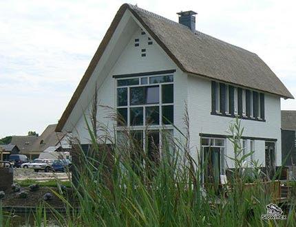 Dwupiętrowy biały dom z przeszkloną sciąną i spadzistym dachem krytym trzciną