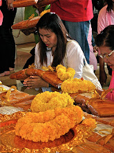 Photo: marigold garlands and a woman offering golden robes in front of the gold Buddha