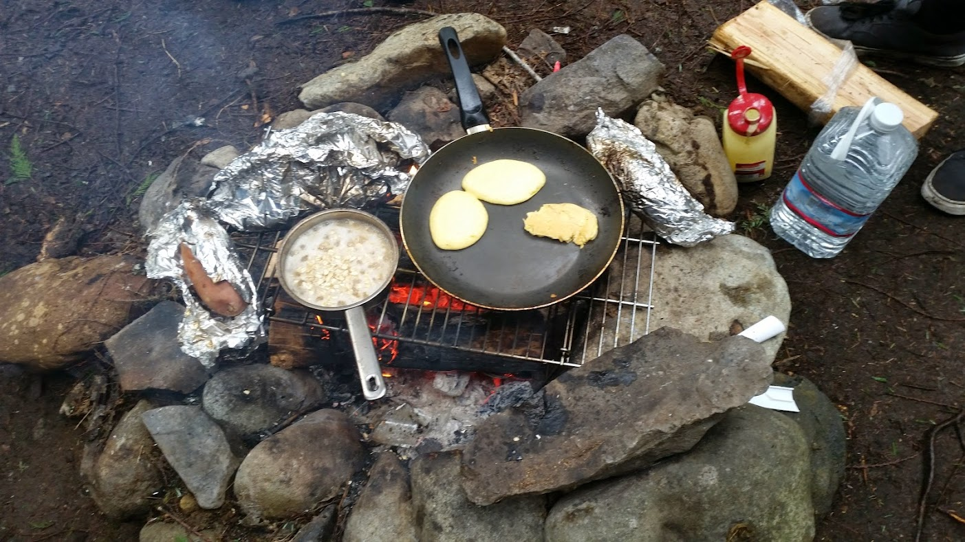 Cornbread pancakes and sweet potatoes over the fire