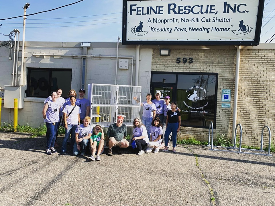 Volunteers from Feline Rescue, a cat rescue organization in Minnesota, stand in front of their shelter with their new cat kennels