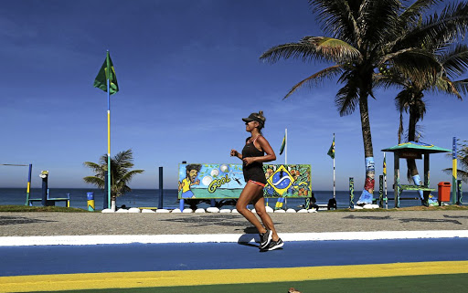 Fifa fever: A woman runs next to graffiti depicting Brazilian player Neymar near Barra da Tijuca in Rio de Janeiro. Picture: REUTERS