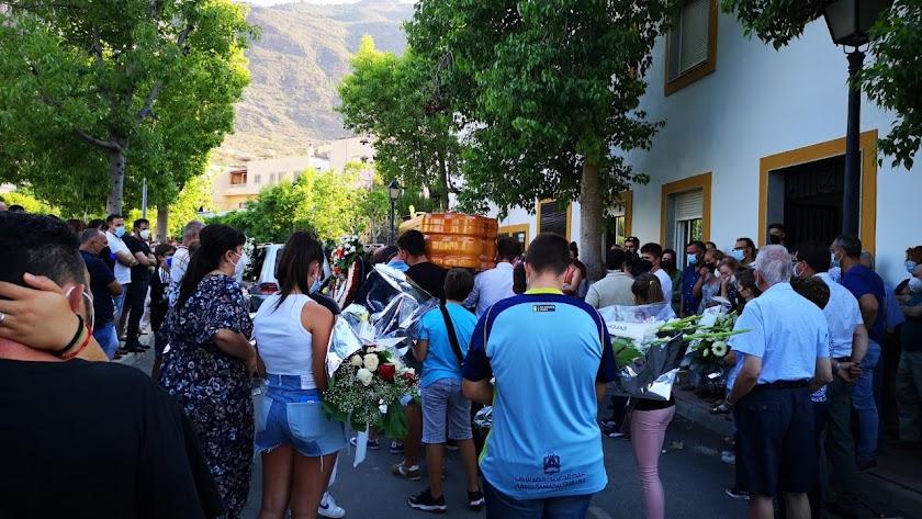 Niños amigos del fallecido portan flores tras el ataúd, camino de la iglesia.
