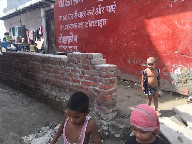 Malnourished kids run around outside a ration shop in India. The lettering on the side of the building is part of an advertisement by a multinational telecom company, peddling cheap phones in the country that hosts the world's largest population of hungry people. Credit: Neeta Lal/IPS