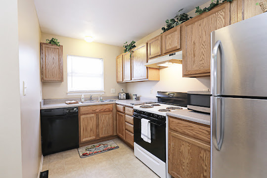 Kitchen with oak cabinets, black and white appliances, and tan tile-inspired flooring