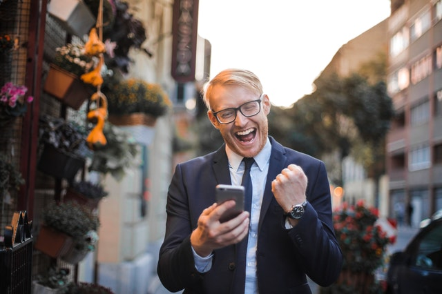 Man cheers at something he reads on his phone.