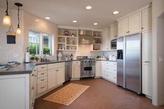 Photo: Interesting backsplash idea in this Santa Barbara,CA, kitchen. The stove wall is completely covered in tile giving the open shelves a unique look.