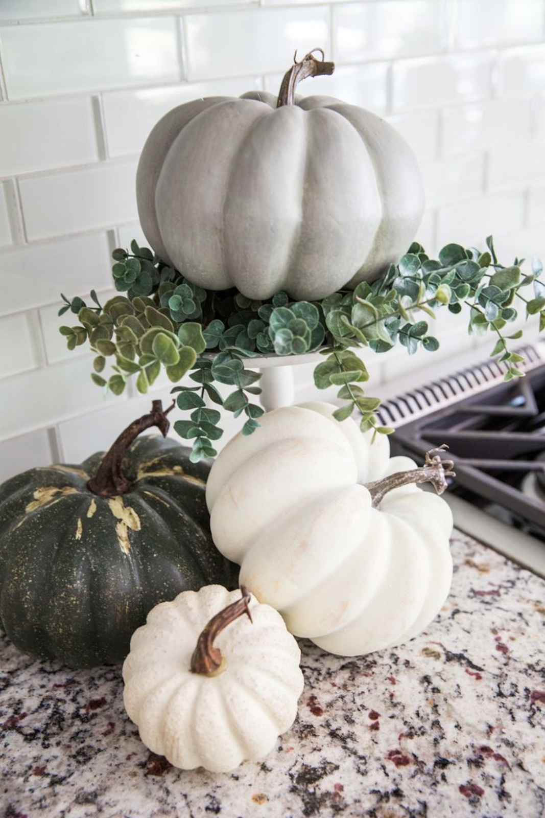 neutral pumpkins stacked on a kitchen countertop