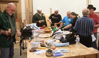 Photo: Lots of action at the tables as visiting demonstrator Tom Wirsing prepares his tools and others are busily engaged at the Show Tell & Ask table.
