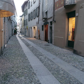 Como, Lombardy, Italy by Serguei Ouklonski - City,  Street & Park  Historic Districts ( city, tourism, house, building, building exterior, cobblestone, road, the way forward, street, narrow, stock, day, italy, architecture, sky, pavement, no person, town, old, built structure, streetview architecture, stone, home, urban, outdoors, light, lombardy, travel, no people )