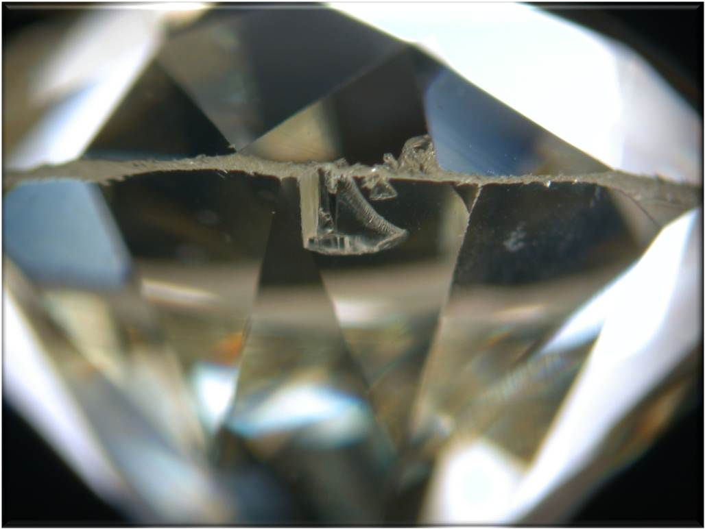 A chip on a diamonds girdle which can be masked by a bezel setting.