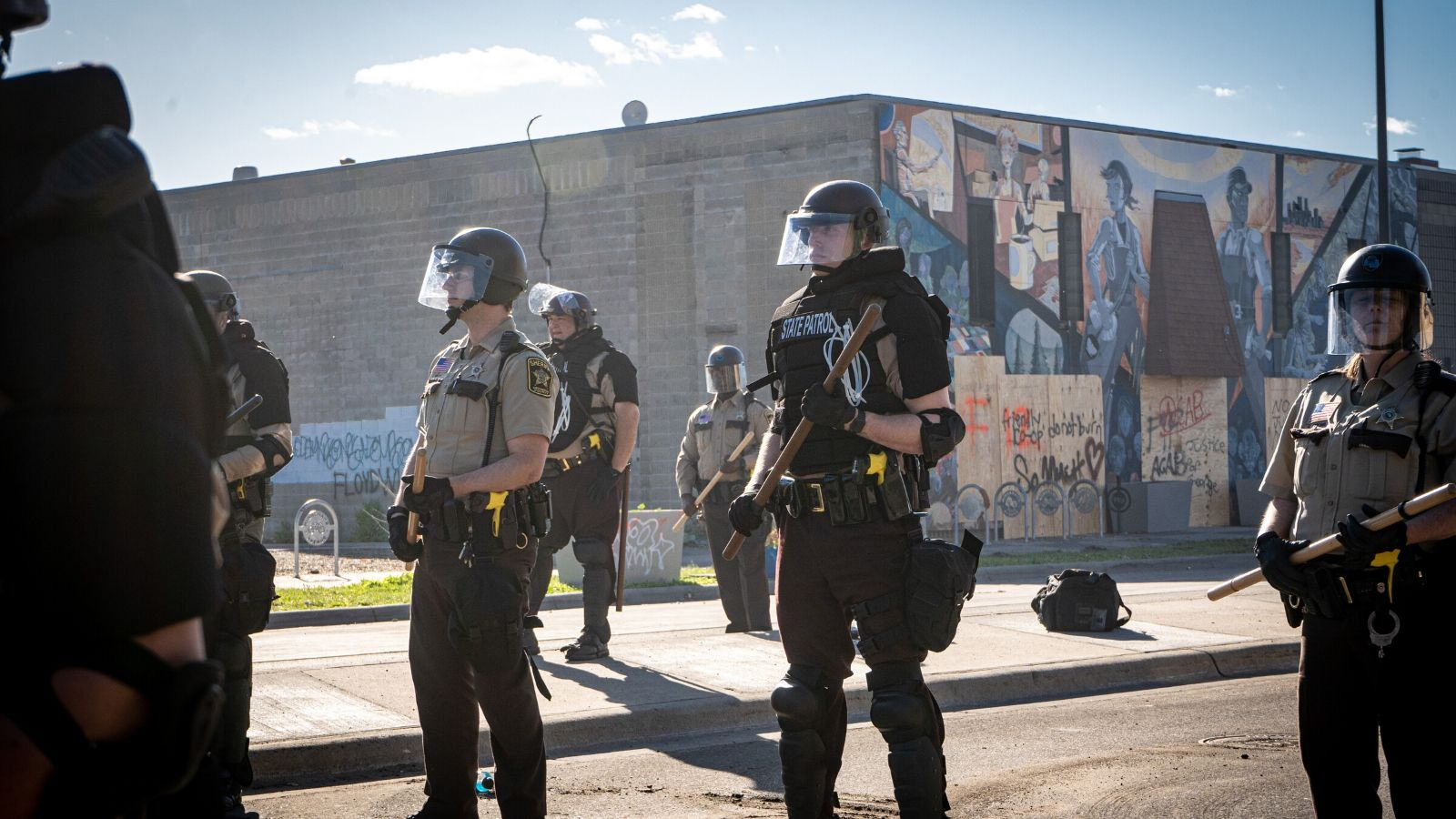 Police stand, armed, in front of protesters at the Black Lives Matter Protest.