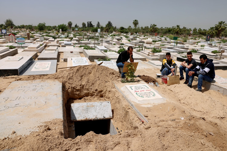 Palestinians wait to bury the body of their relative, who died after from complications of COVID-19, at a cemetery, east of Gaza City on April 20 2021. Picture taken April 20, 2021. Picture: REUTERS/MOHAMMED SALEM