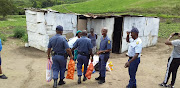 KZN police officers carry groceries to the home of a gogo in Umbumbulu, after her granddaughter asked officers for help when she was kicked out of her mother's house following an argument.