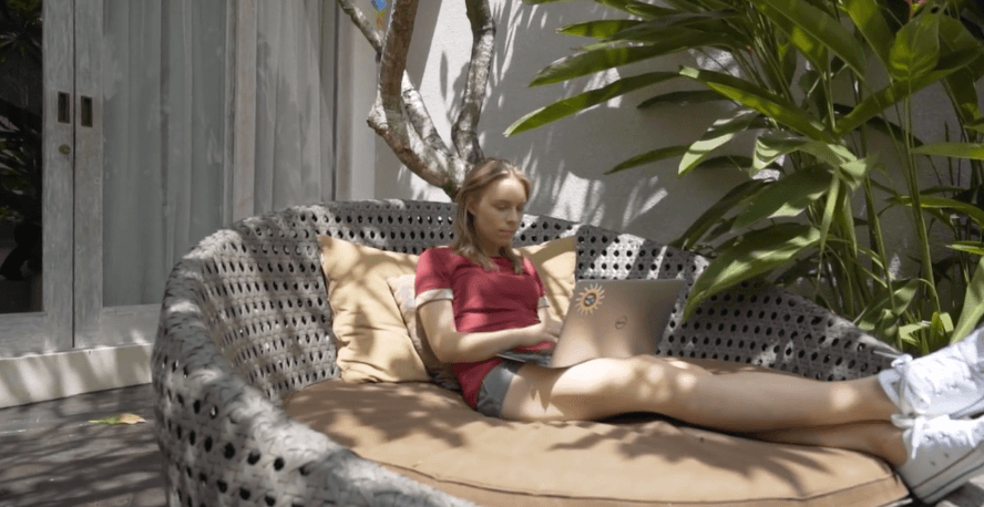 sarah chrisp lounging with her laptop on a huge seat outdoors