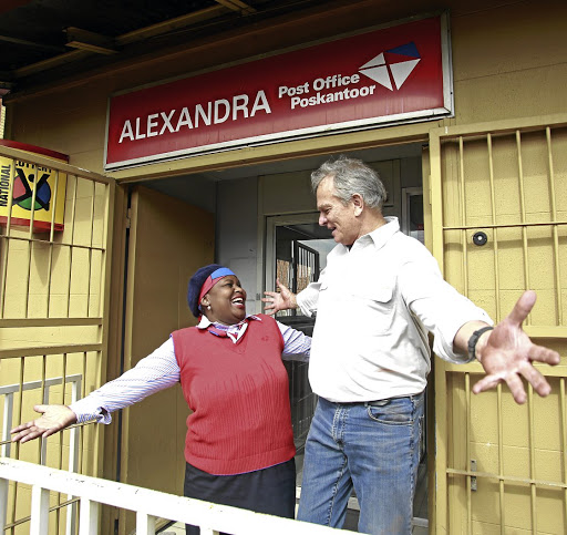 Step in right direction: South African Post Office CEO Mark Barnes, right, greets employee Gloria Malatji on his visit to a branch in Alexandra, Johannesburg. Picture: SUNDAY TIMES