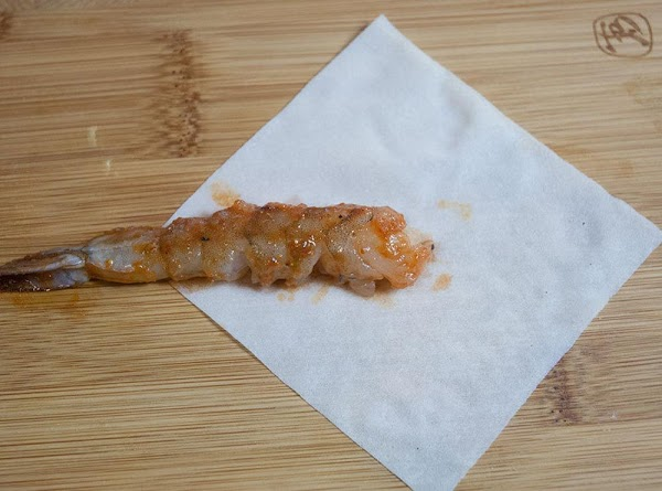 Lay a wrapper on a clean work surface and place a single shrimp horizontally...