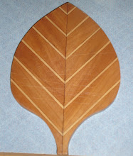 Photo: This leaf motif was from WoodWorker's magazine. First cut strips of various widths. Glue up into a rectangle, alternating colors. Sand the surface. Cut the rectangle on the diagonal. Then pad saw the two identical mirror image halves with a band saw into a pretty leaf shape. Edge sand with a drum. Groove and spline the mating edges. Glue the two halves together. The original design called for a contrasting strip down the middle. Once I stooped trying to do that I was able to finish the project. This was my first time using two-part waterproof glue. Good stuff, but messy and impossible to clean up with soap and water! Finish is too many thick coats of polyurethane, not enough sanding. I am still learning. This cutting board only cost about 10X what a store bought one would. And took years to finish, but I did finish it.