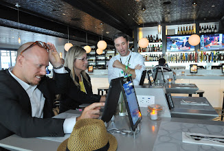 """Photo: Newly weds, Kelly Tribell, left, and his wife Sarah Lewis, of Fayetteville, Arkanas, get assistance ordering lunch using an Ipad from waiter Antonio Collodoro, right, at Mimosa, a new restaurant on Concourse G at the Minneapolis St. Paul airport  on September 5, 2012. The couple were on their honeymoon en route to Marseille, France. """"I'm intrigued by the setting here. You can order online,"""" said Tribell."""
