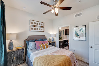 Model bedroom with ceiling fan and carpet