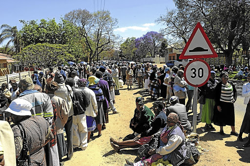 Scores of people queue outside the South African Social Security Agency building in the Capricorn district of Limpopo to collect their grants. Picture: ELIJAR MUSHIANA