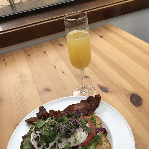 Gluten free avocado toast with an added poached egg and bacon. Drink was the elderflower mimosa! Highly recommend