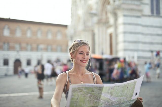A blonde woman looking at a map