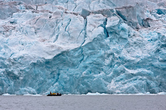 Photo: This is the front wall of the 14th of July Glacier in Spitsbergen. As you can see from the Zodiac, it's pretty big! The Zodiac's probably a bit too close for comfort really. It's pretty common for large chunks of ice to break off the front wall in a process known as calving. Aside from the direct danger of the falling ice, it can generate large waves that could easily swamp a boat like this.  During our trip we did witness quite a few instances of ice calving off the front of glaciers and it was always a spectacular sight. Normally you'd hear a crack and boom before the ice started falling, so even if you weren't facing the right way you'd have a split second to turn around and watch.