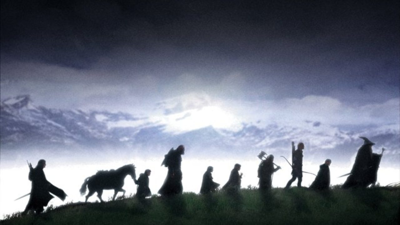 The Fellowship of the Ring walking in silhouette on a hill.