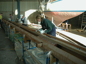 Photo: Gluening the masts with huge amounts of epoxi and every helping hand we could get!