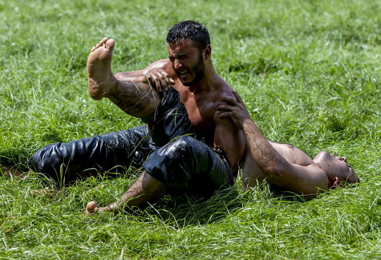 A wrestler tosses his opponent to the ground at the Kirkpinar Turkish Oil Wrestling Festival in Edirne, Turkey.