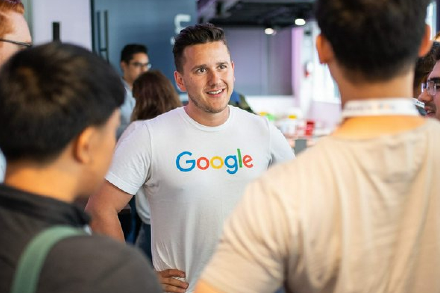 Man wearing a Google tshirt talking to a group of people.
