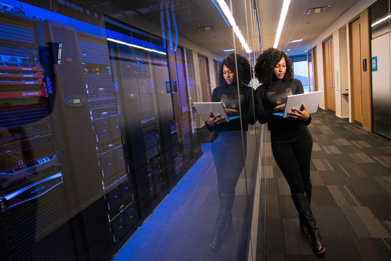 Une fille dans une chambre de serveurs avec un ordinateur
