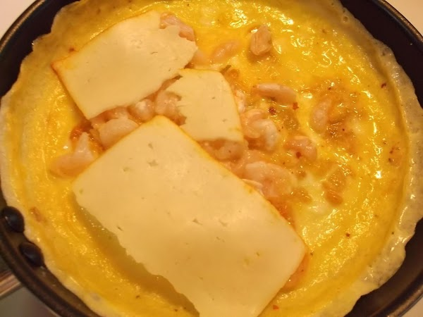 Tear or cut cheese to evenly cover 1/2 the omelette; lay cheese on omelette.