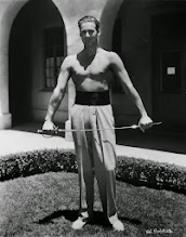 Photo: Erroll Flynn was noted for his athleticism, and that provides the excuse for presenting him cheerfully half-naked. The rapier becomes an excuse for the bare chest, as if he's exercising--although I am not aware of any benefit to fencing while shirtless.