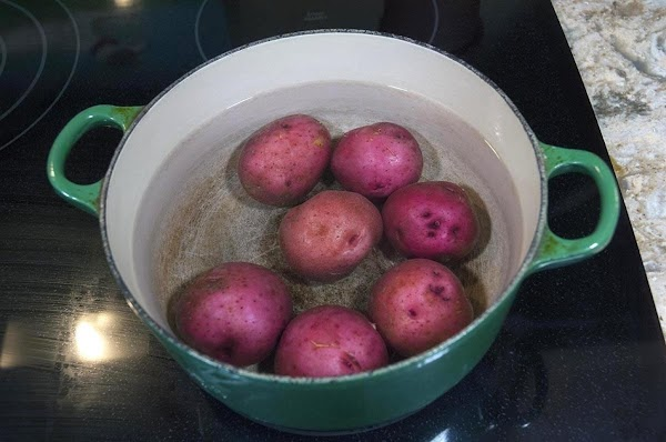 Scrub the red potatoes clean, add to a pot, and cover with cold water.