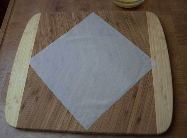Place a wrapper on a dry surface with one of the points toward you,...