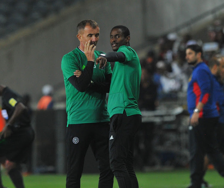 Orlando Pirates head coach Milutin Sredojevic (L) in a discussion with his assistant Rulani Mokwena (R) during a Caf Champions League group stage match against hholder Esperance at Orlando Stadium on February 2 2019.