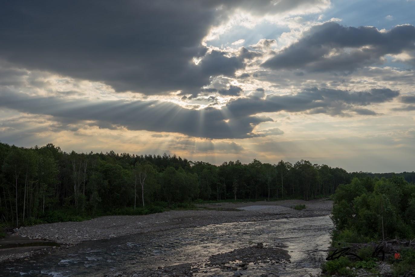 藍墨茶色の雲から降り注ぐ朝陽