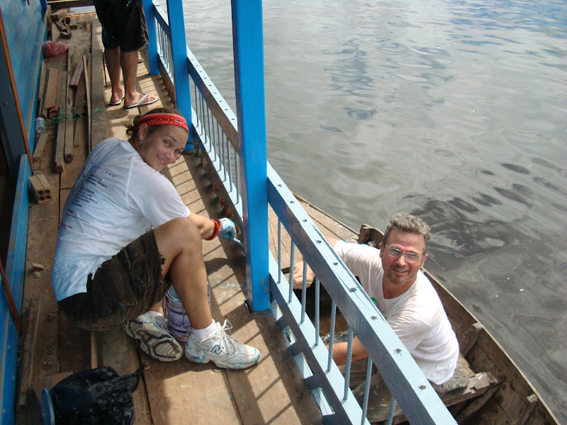 Photo: Columbia residents Cristi Cook and Brian Anderson are working together to paint the Floating Learning Center in Cambodia