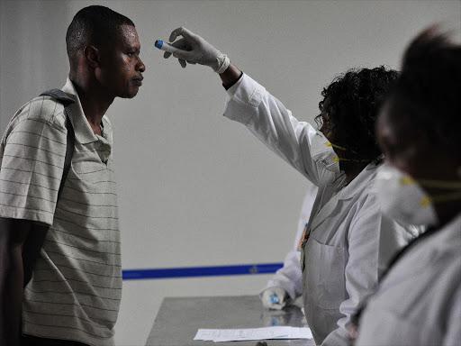 Health officials take passengers' temperature on arrival at the Jomo Kenyatta International Airport, Nairobi, on August 14, 2014 /FILE