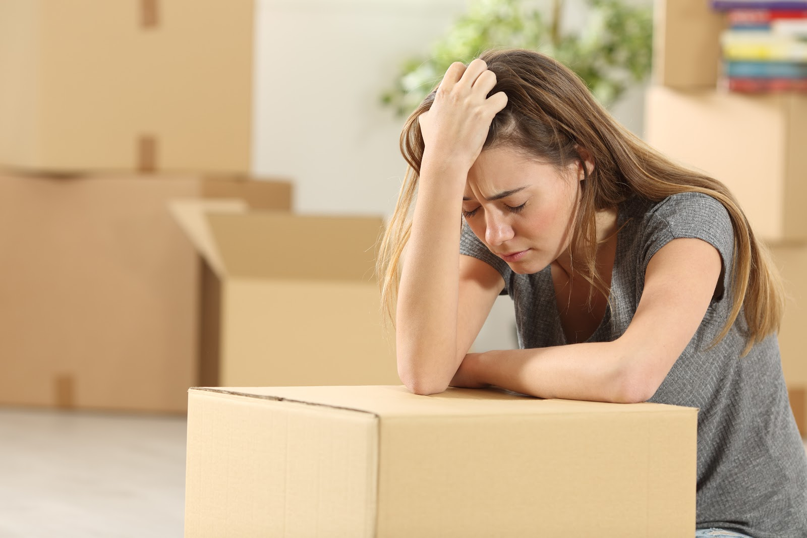A woman with her eyes closed looking very stressed leaning on a moving box