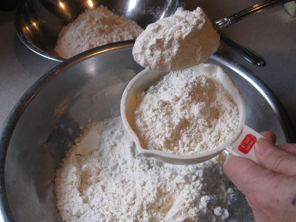 Pour white flour into a large bowl, then scoop flour with a big spoon...